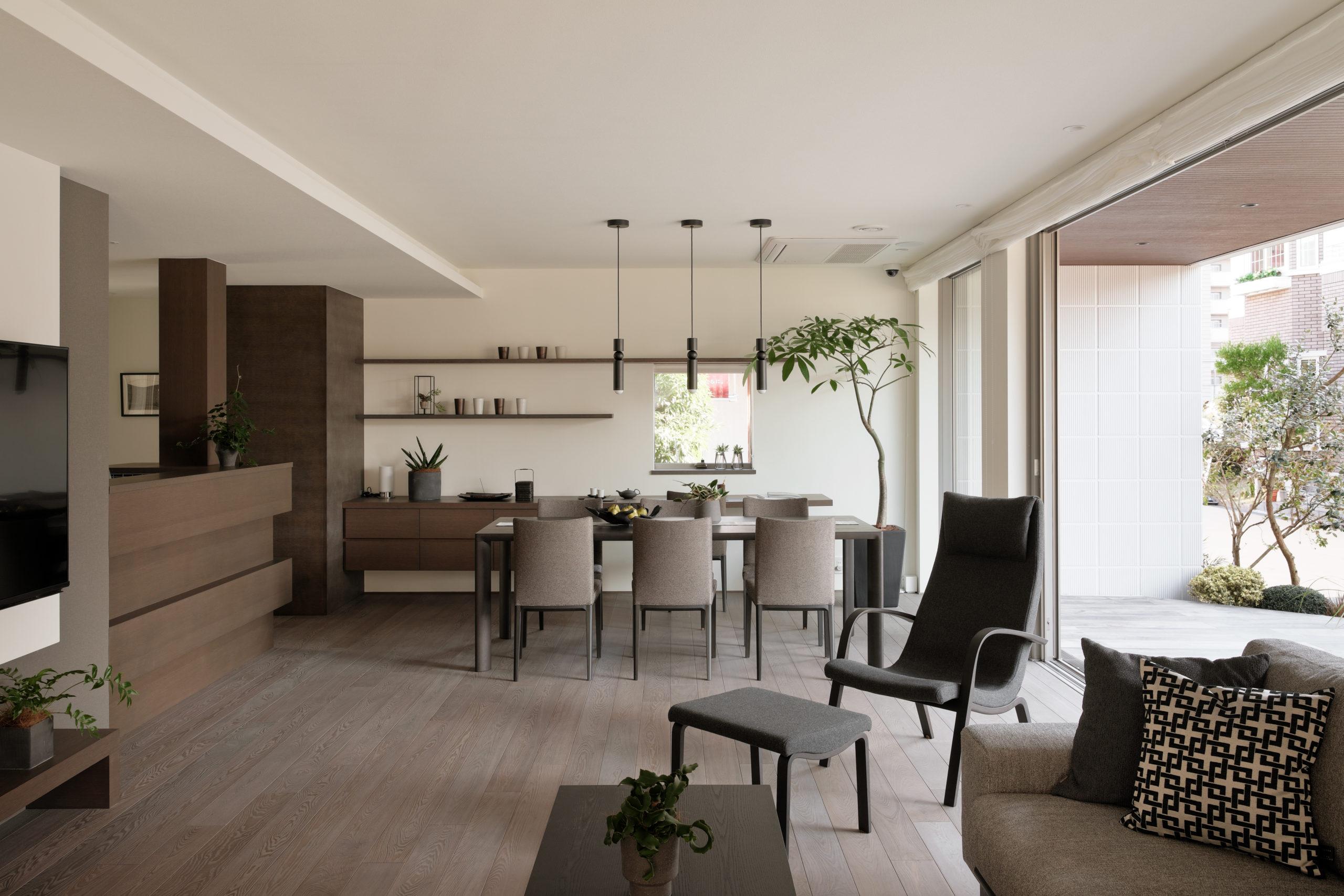 親世帯のLDKはグレイッシュトーンで落着いた雰囲気に、天井に間接照明を設置しひかりの帯がほっとする空間を演出しています。