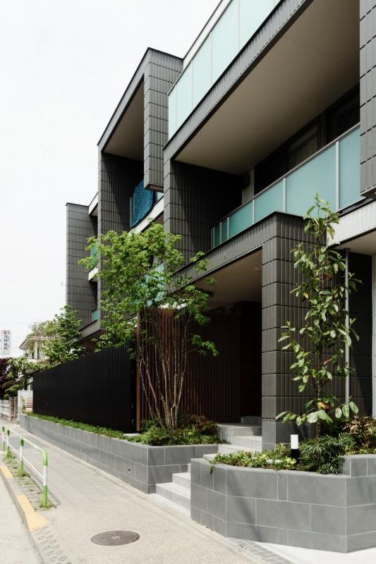 通りから、ごみ箱や自転車置き場などが見えないよう配置し、無機質な建物にグリーンで温もりを加えています