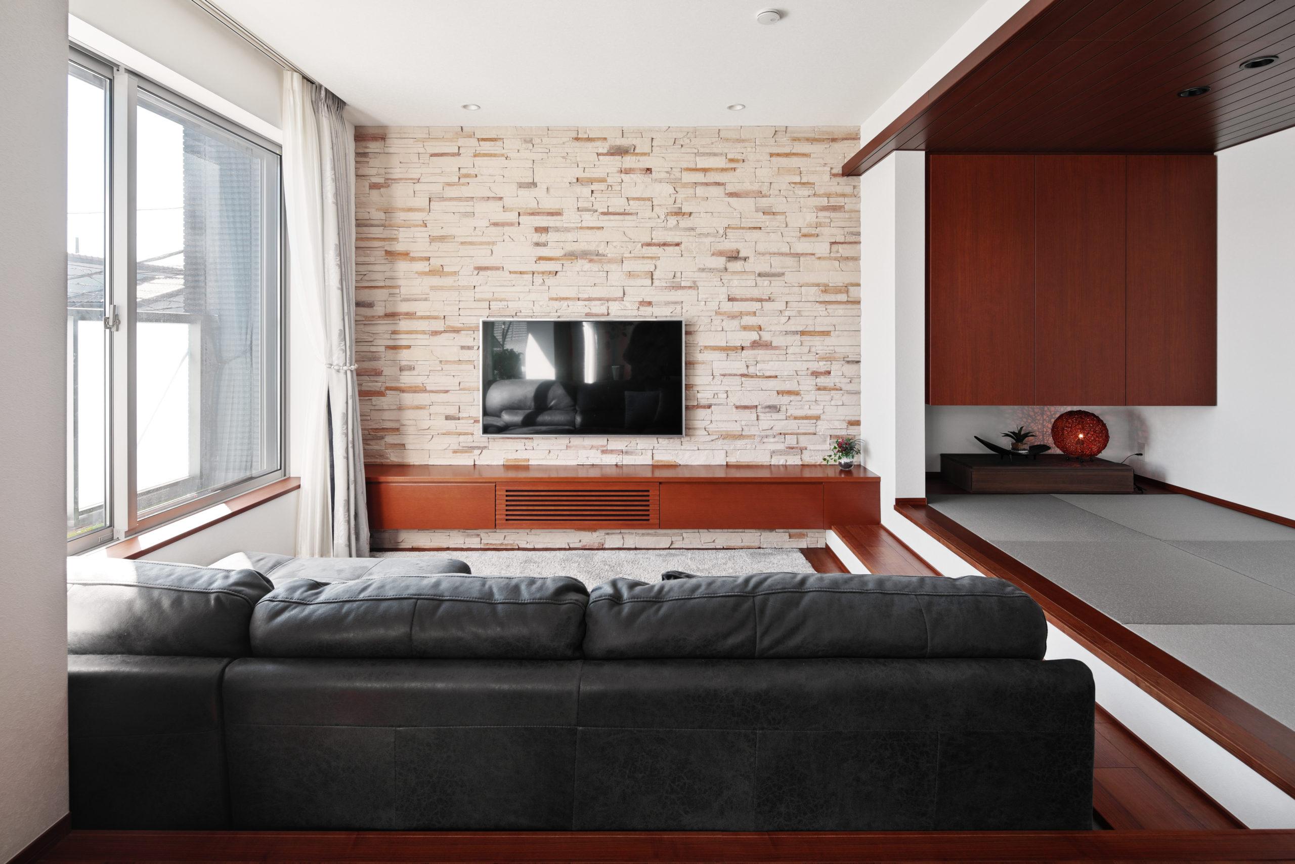 ダウンフロアリビングのTV背面の壁は凸凹感のあるタイル仕上げ