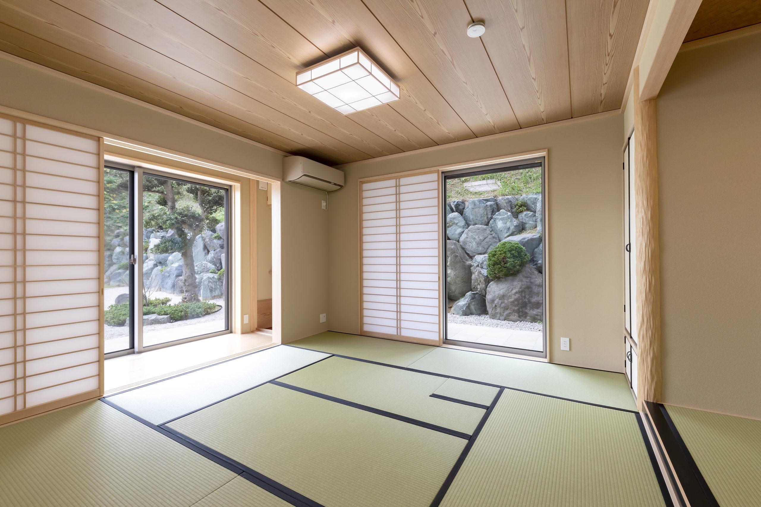 床の間、水屋、炉切りのある本格的な茶室。窓から見える石積が映える