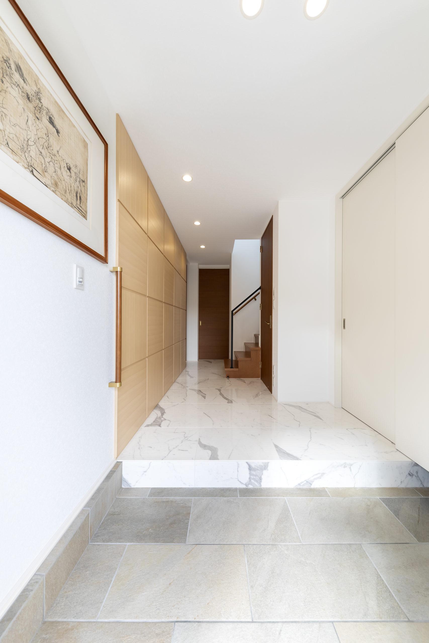 白基調に木調パネルが映える玄関ホール