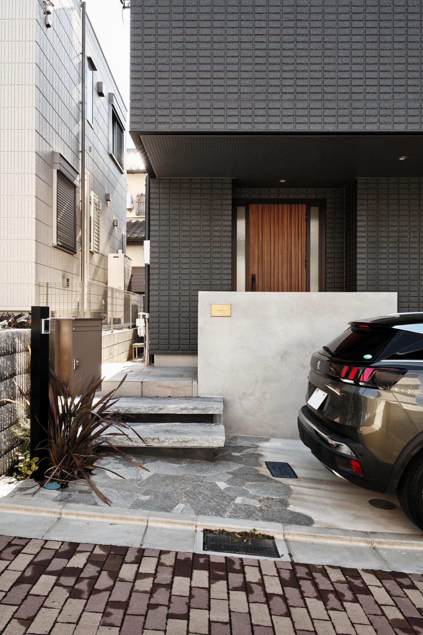 自然石調のアプローチと玄関前の塗り壁が高級感を演出します