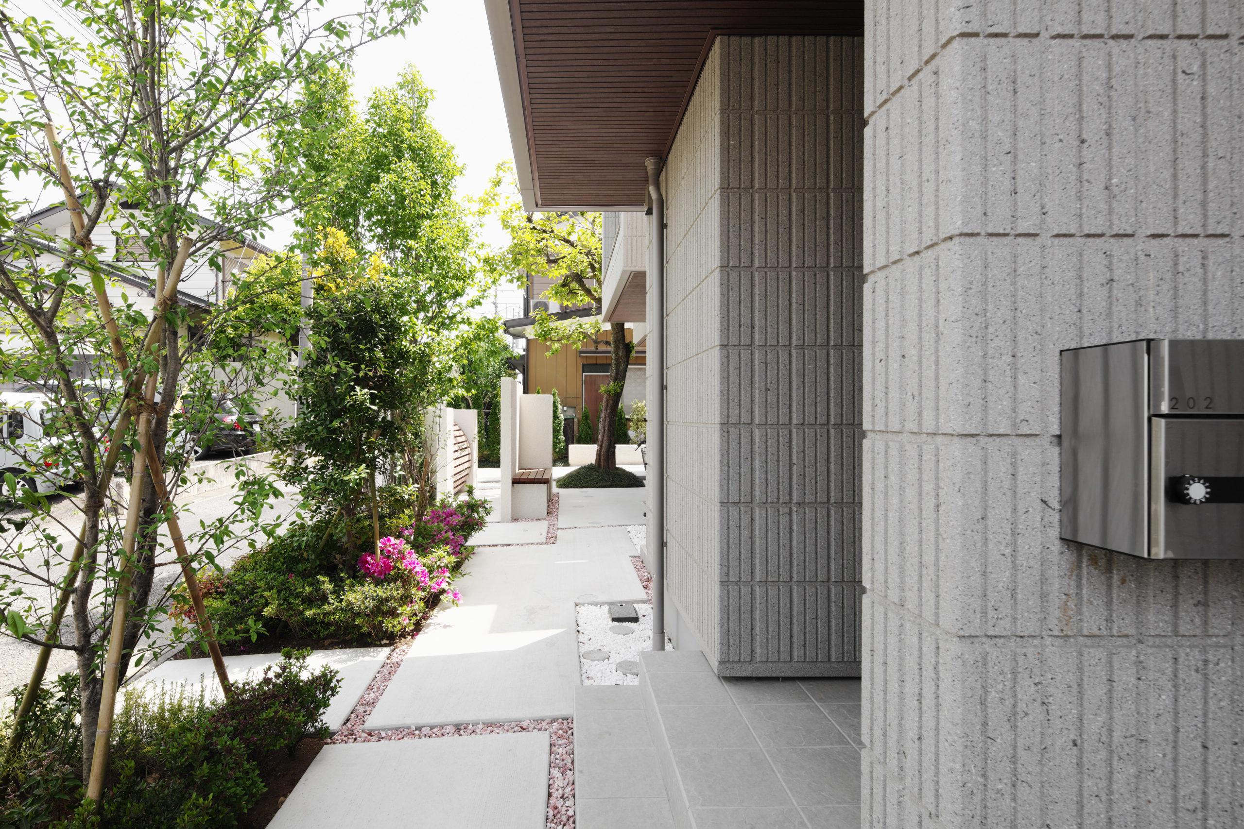 植栽の間を抜け、各住戸独立した導線を確保。床材と床材をBrown gravelでアクセントをつけ、プライベート感を演出。